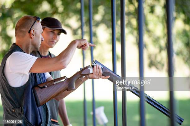 instructor teaching adult woman skeet shooting and rifle handling - shotgun stock pictures, royalty-free photos & images