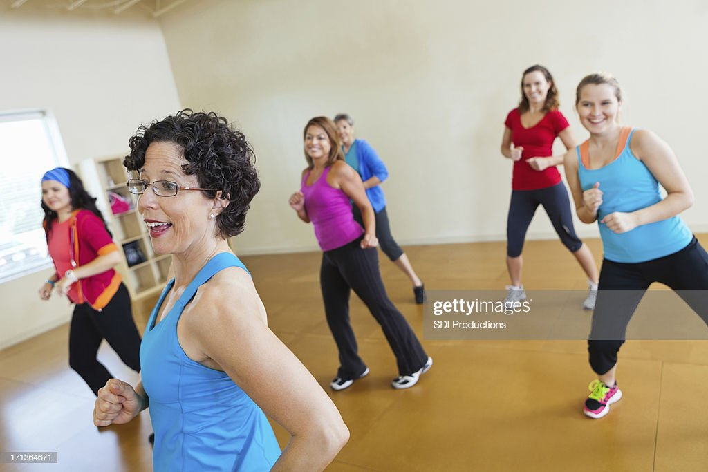 Instructor teaching group of healthy women dance fitness : Stock Photo