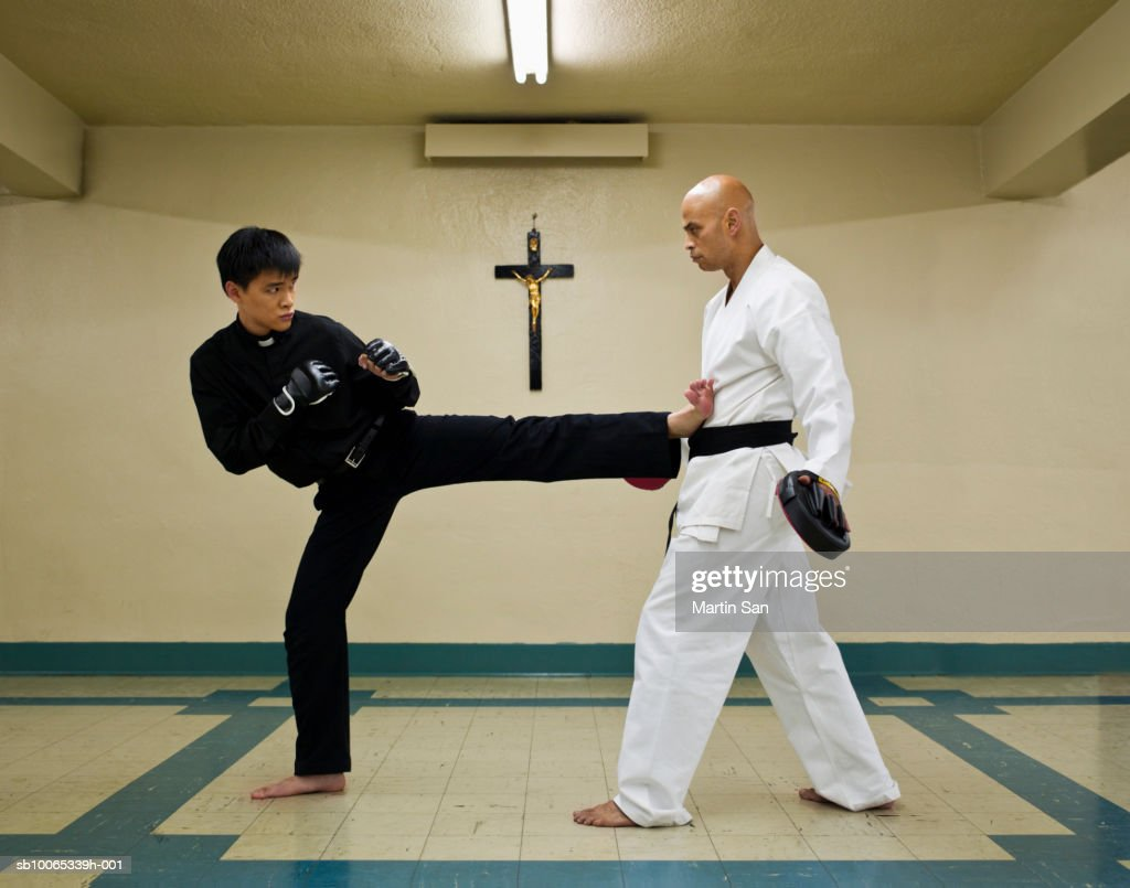 Instructor teaching martial arts to young priest : Foto stock