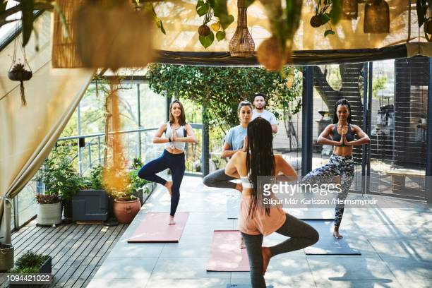 instructor teaching tree pose to clients on porch - tree position stock photos and pictures