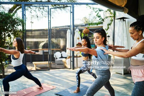 instructor teaching warrior position on porch - yoga teacher stock pictures, royalty-free photos & images