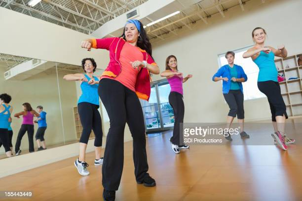 Instructor teaching women fitness dance moves in class