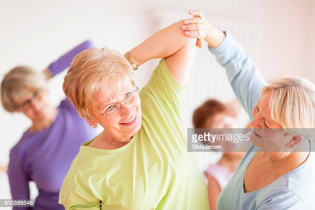 instructor with active senior women in yoga class