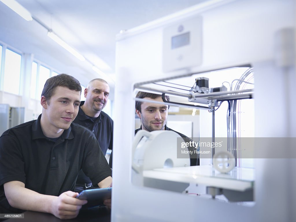Instructor with apprentices and 3D printing machine : Stock Photo
