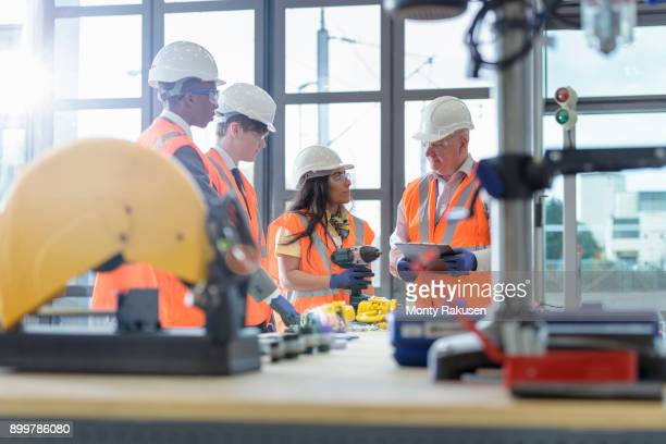 Instructor with apprentices in workshop of railway engineering facility