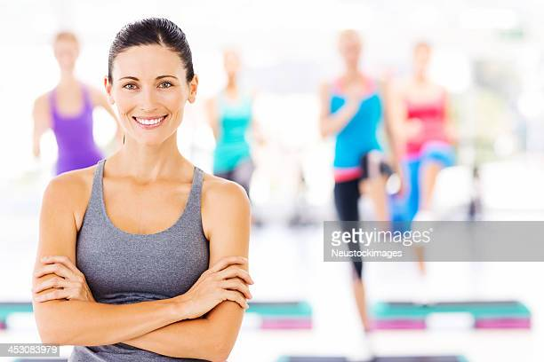 Instructor With Class Exercising In At Health Club
