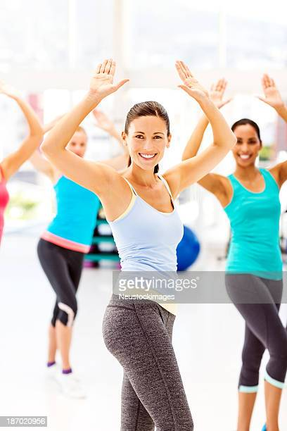 Instructor With Customers Practicing Aerobic Dance In Gym