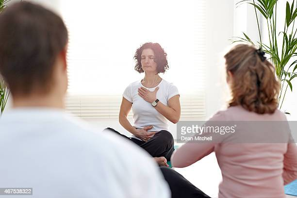 instructor with group of people in yoga class - yoga teacher stock pictures, royalty-free photos & images