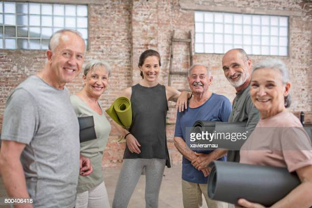 Instructor with happy senior people in yoga class