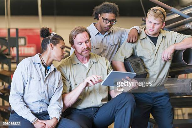 Instructor with trainees in welding school
