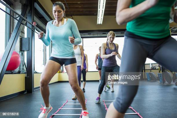 instructor with women jumping over agility ladder in gym - small group of people stock pictures, royalty-free photos & images