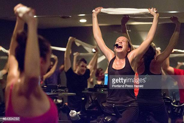 Instructor/trainer Carolyn Williams holds a towel over her head and sings along to a song as she leads a 6 am spin class at Reve Cycling Studio...