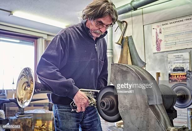 Instrument maker polishing trumpet in workshop