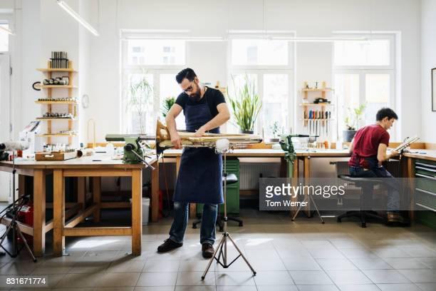Instrument Maker Working In Clean, Organised Workshop Alongside Apprentice