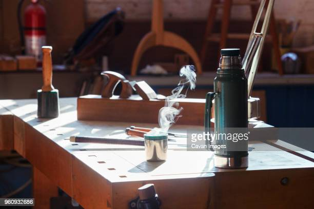 insulated drink container with work tools on table in workshop - flask stock pictures, royalty-free photos & images