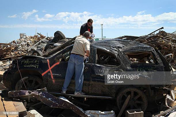 Insurance adjusters inspect damage to a vehicle that came to rest on debris of a collapsed strip mall along the I35 commercial strip after a tornado...