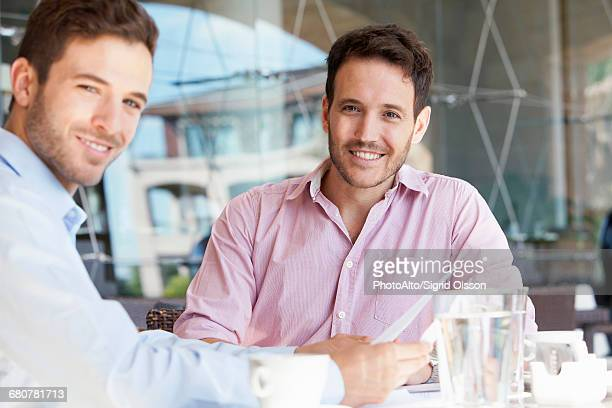 Insurance agent discussing contract with client over coffee
