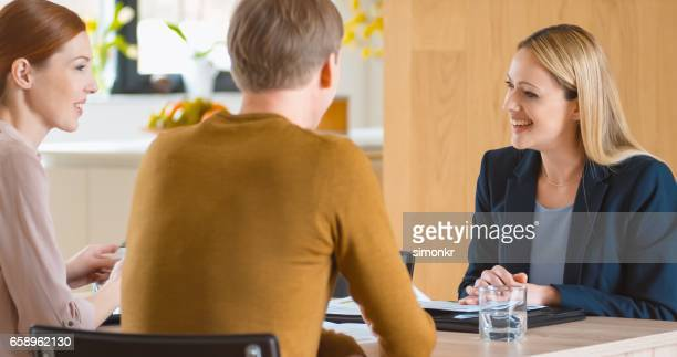 insurance agent discussing with couple - ginger banks stock pictures, royalty-free photos & images