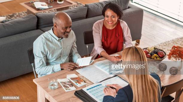 Insurance agent discussing with mature couple