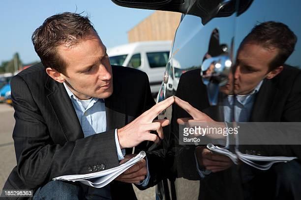 Insurance agent inspecting damage on a car