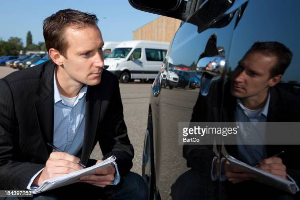 Insurance agent looks at car