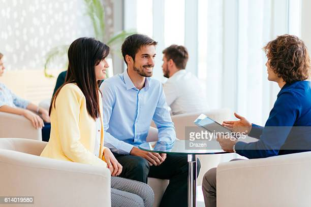 Insurance agent selling insurance policy to young couple