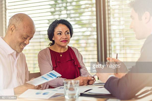 Insurance agent talking to older couple of african ethnicity