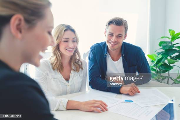 insurance agent with couple looking through documents. - medical insurance stock pictures, royalty-free photos & images