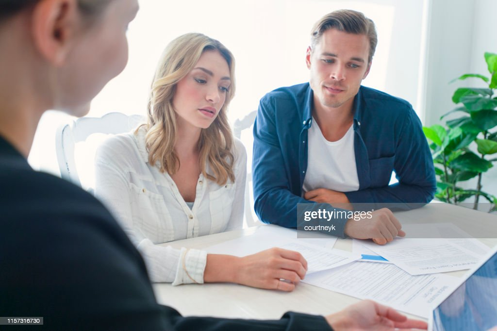 Insurance agent with couple looking through documents. : Stock Photo