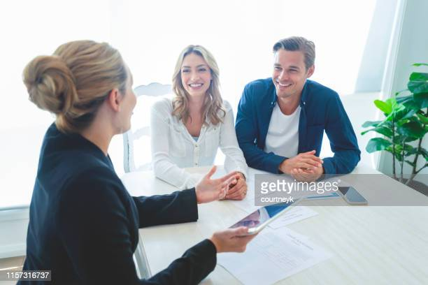 insurance agent with couple looking through documents. - financial advisor stock pictures, royalty-free photos & images