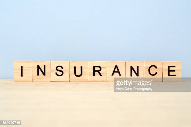 insurance word on wooden tile block - insurance stock pictures, royalty-free photos & images