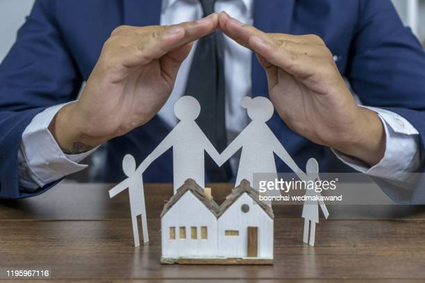 insurer protecting a family with his hands; multiple exposure - life insurance stock pictures, royalty-free photos & images