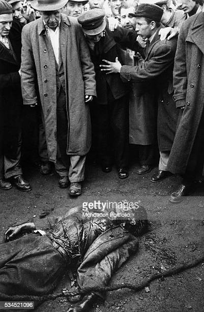 Insurgents watcing the corpse of a colonel of the Hungarian secret police dead during the clashes Budapest November 1956