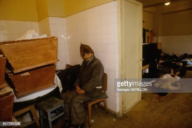 Insurrection a Bucarest un vieil homme assis a cote de cadavres dans une morgue de fortune le 25 decembre 1989 a Bucarest Roumanie