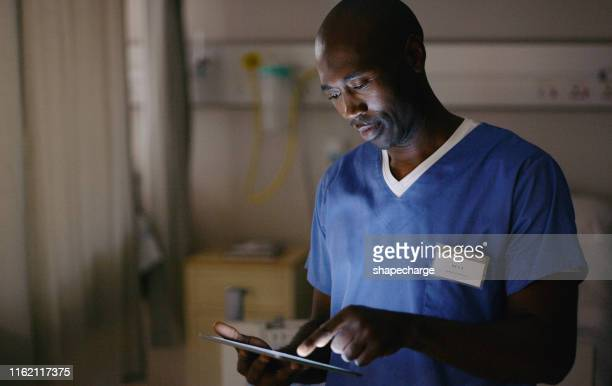 integrating the modern and medical worlds - male nurse stock pictures, royalty-free photos & images