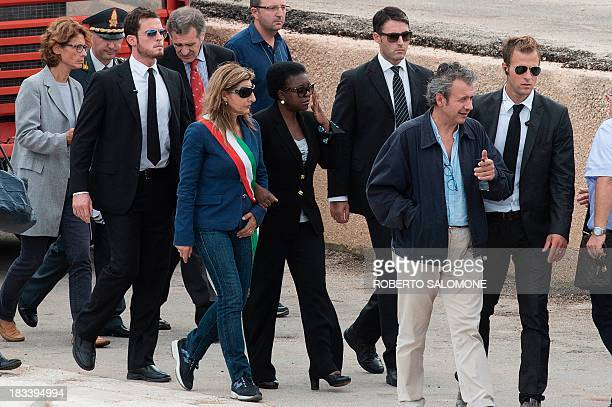 Integration Minister Cecile Kyenge arrives in the harbour of Lampedusa with the mayor of Lampedusa Giuseppina Nicolini on October 6 after divers...