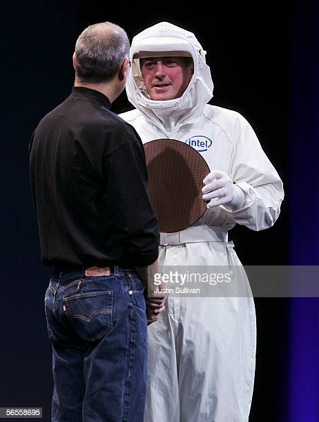 Intel CEO Paul Otellini wears a clean suit as he shows an Intel chip to Apple CEO Steve Jobs during his keynote address at the 2006 Macworld January...