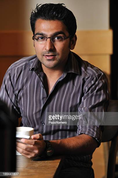 intellectual pakistani man at a cafe - handsome pakistani men stock photos and pictures