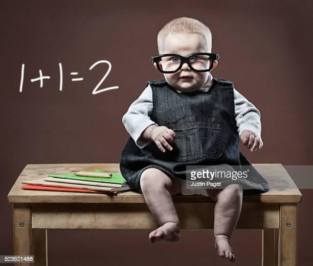 Intelligent baby girl (6-12) wearing glasses sitting on desk