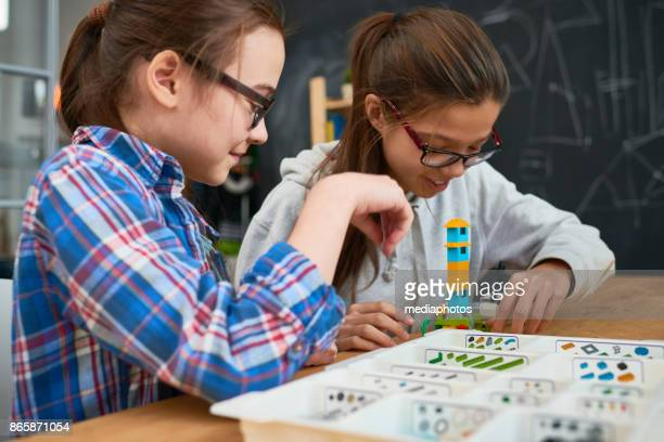 Intelligent girls making tower from building blocks
