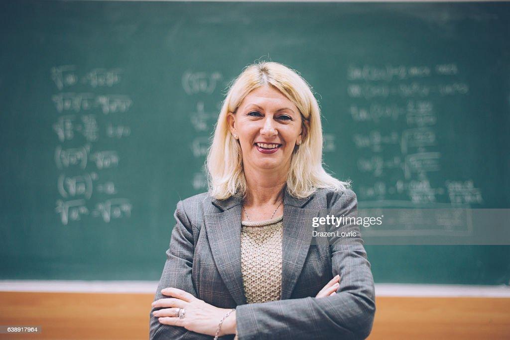 Intelligent matur female math professor in classroom : Stock Photo