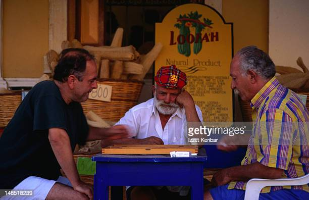 Intense game of backgammon in play at a Taverna on Symi island, part of the Dodecanese. In the background is a sign extolling the virtues of a local product - the Loofah.