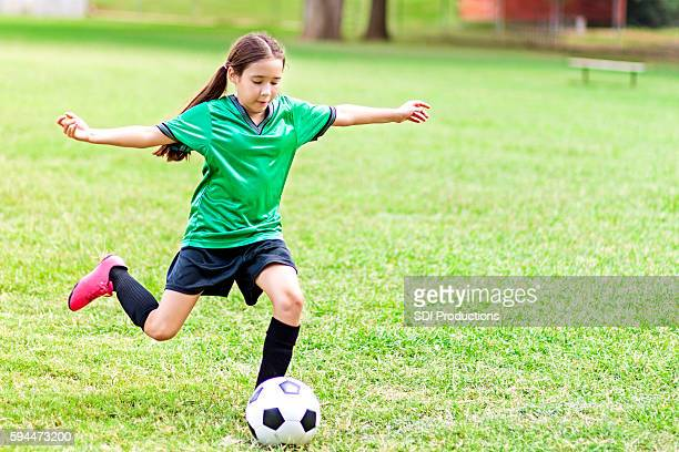 Intense Hispanic preteen girl kicks soccer ball