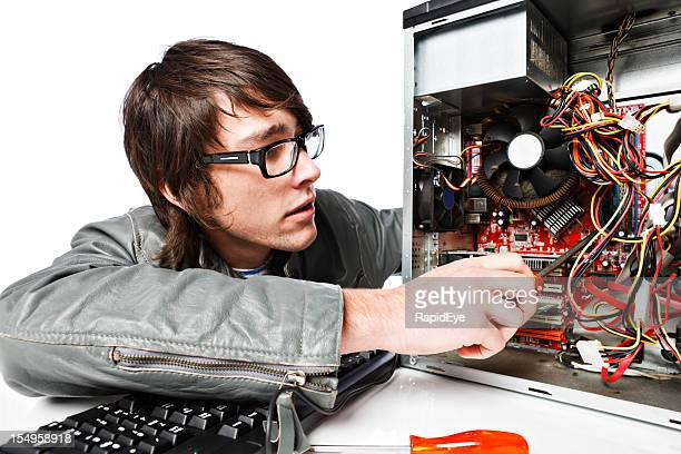 Intense young IT professional repairs PC