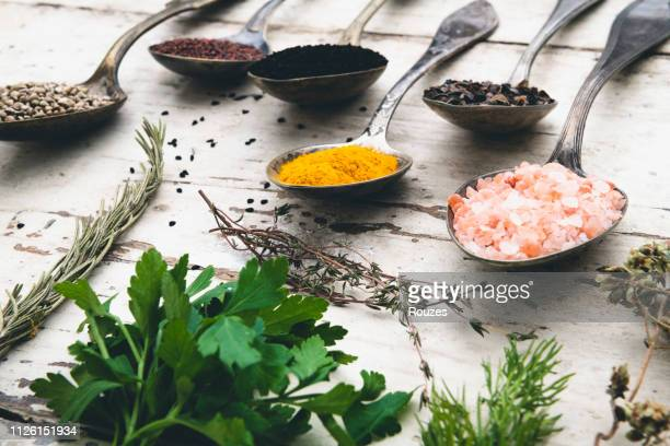 intensive condiments on old spoons - herb stock pictures, royalty-free photos & images