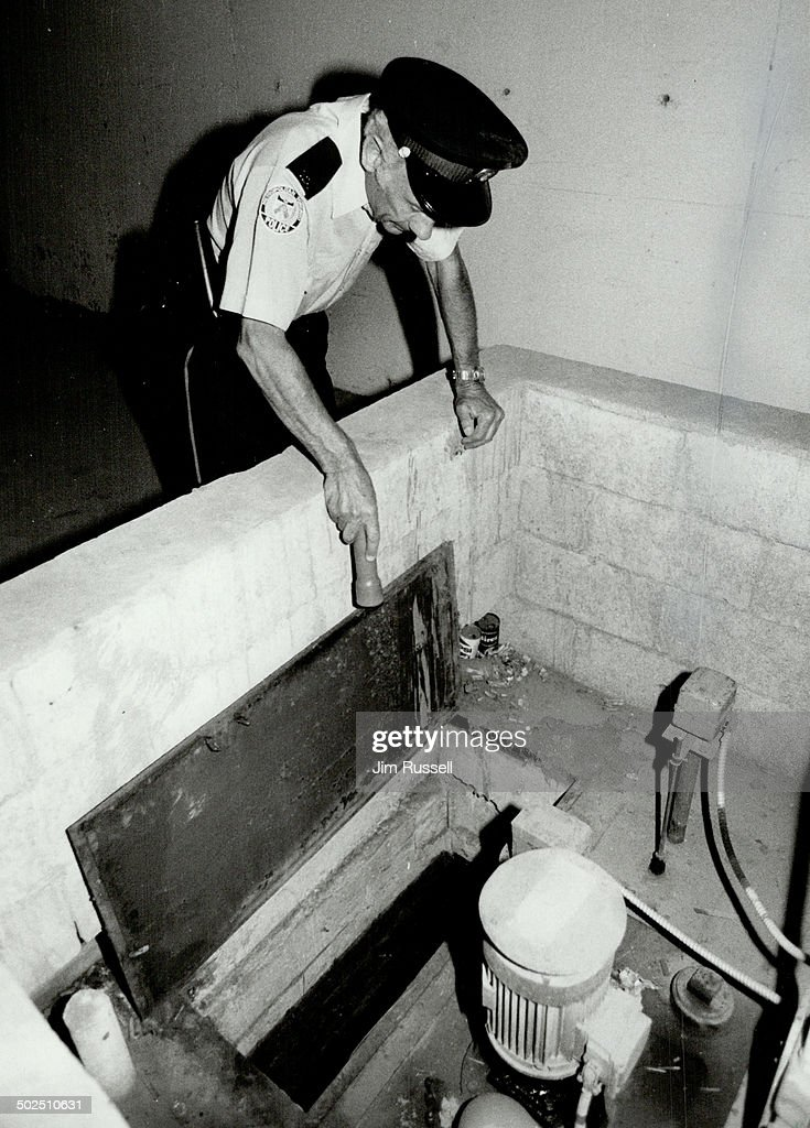 Metro police constable Terry Donovan (left) inspects the sump pump collecting basin in the parking garage of the condominium where missing Nicole Morin lives. Other detectives such as Constable John Grima with tract dog Bronc spent the day searching for Nicole in the Centennial Park area just west of the girl's home on the West Mall.