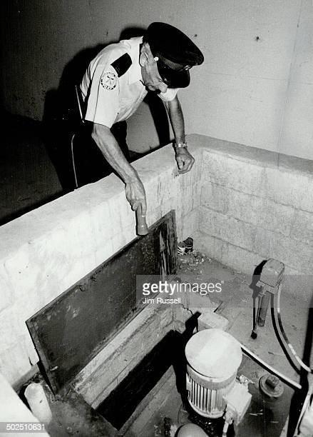 Intensive search Metro police constable Terry Donovan inspects the sump pump collecting basin in the parking garage of the condominium where missing...