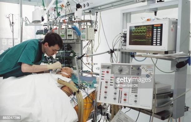 Intensivstation ein älterer Patient liegt in einem modernen Krankenbett und ist mit Schläuchen und Kabeln an medizinische Apparaturen angeschlossen...