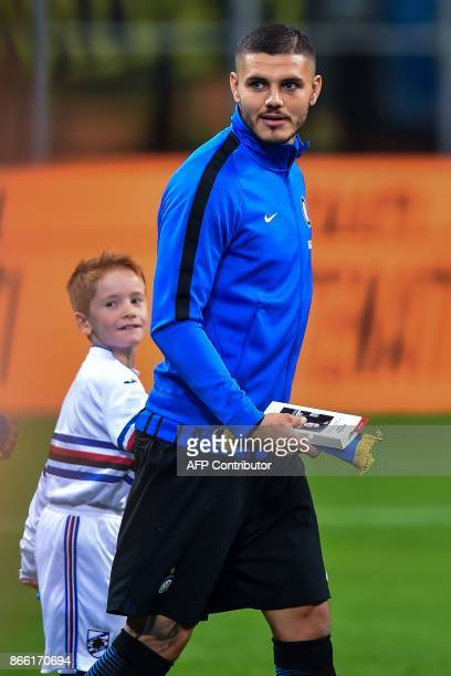 Inter Milan captain Mauro Icardi holds a copy of The Diary of Anne Frank before to give it to child mascot accompanying him onto the pitch at the San...