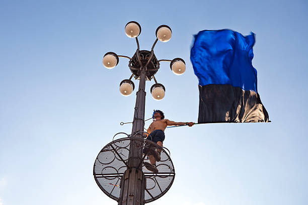 Inter Milan football supporter waving flag from street light tower in Piazza del Duomo.